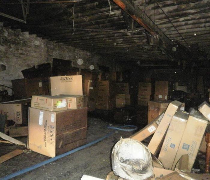 Warehouse filled with contents with extensive fire damage in walls and ceiling