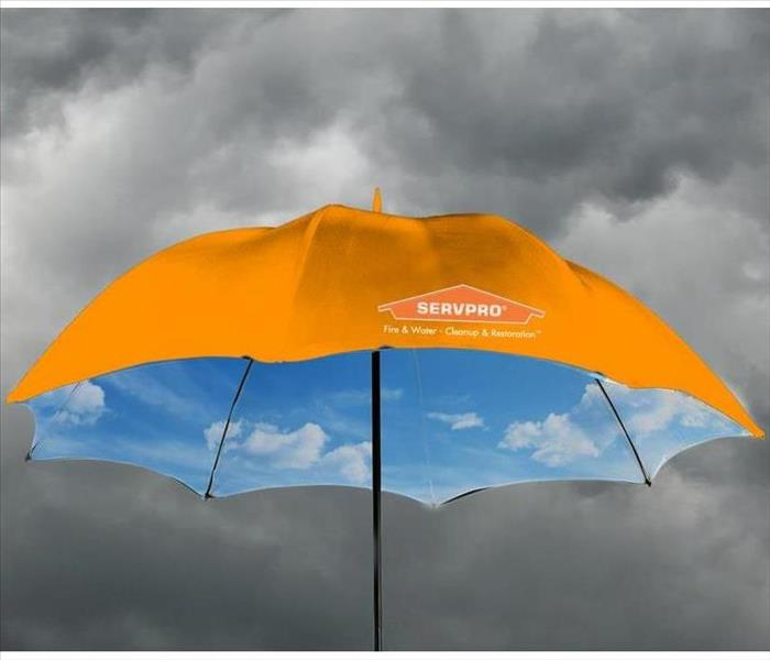 Stormy skies with an umbrella with SERVPRO logo and inside showing blue skies