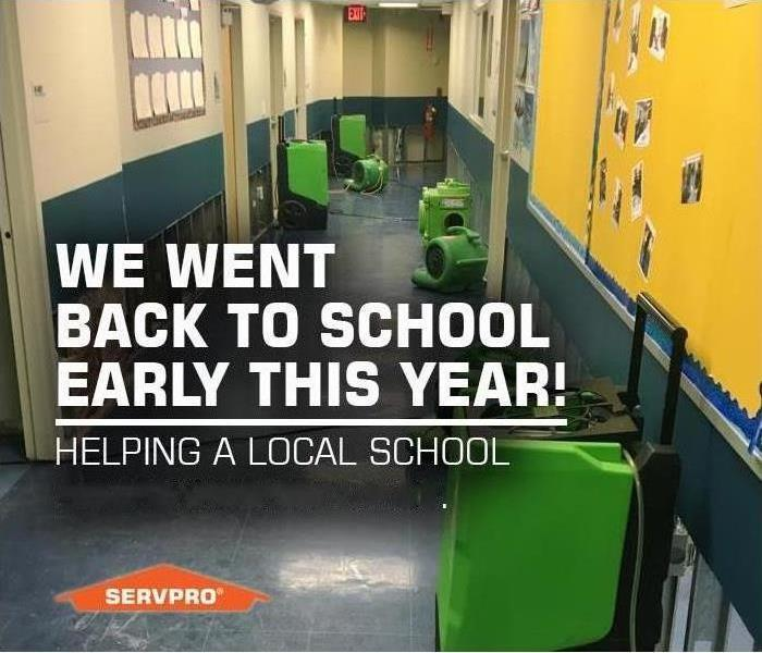 Hallway in a school with air movers. SERVPRO logo and text We went back to school early this year!