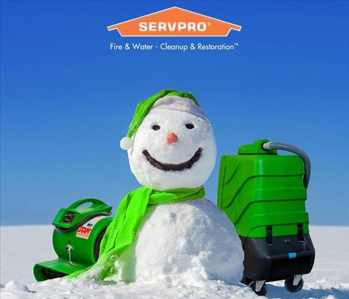 A snowman with a green scarf and hat with SERVPRO equipment on a sunny day