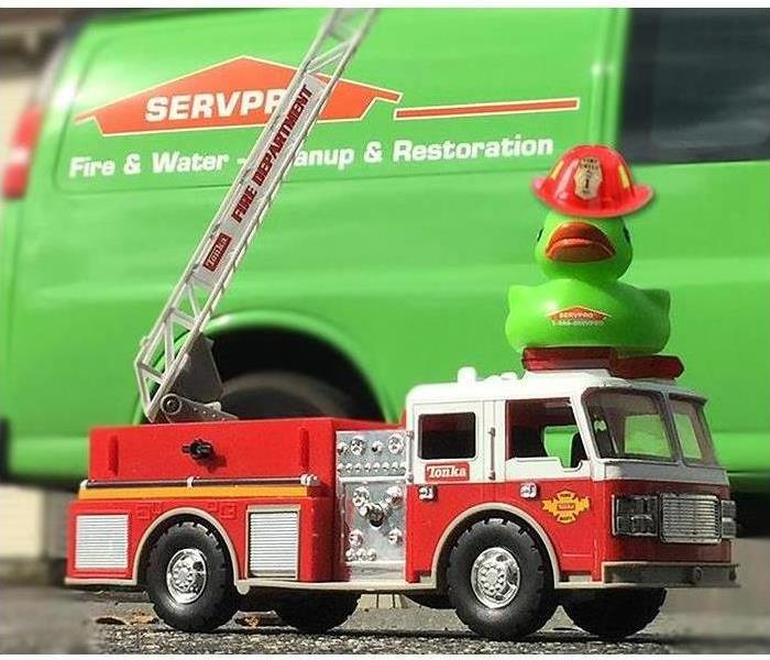 A toy fire truck with the SERVPRO duck on top of it and a SERVPRO van in background